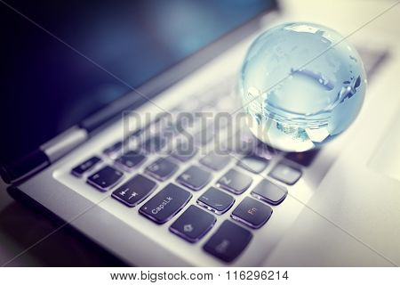 Glass crystal globe on laptop keyboard concept for global communication and business