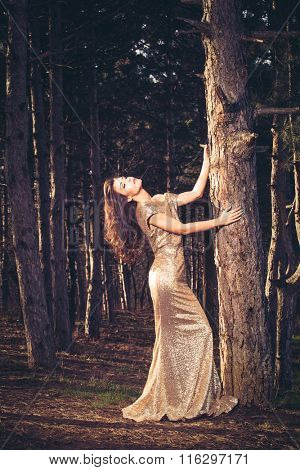 beautiful young woman in elegant glittering golden dress  in wood full body shot