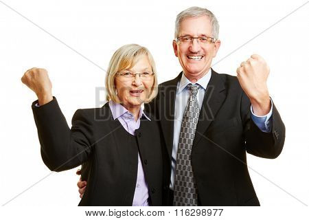 Cheering old happy senior couple clenching their fists together
