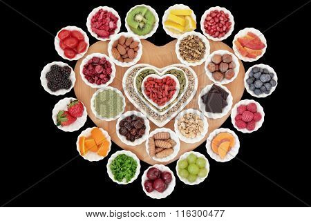 Health and superfood selection in heart and round shaped porcelain bowls on a wooden board over black background with copy space. High in vitamins and antioxidants.