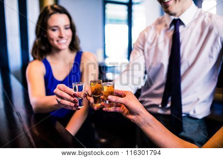 Friends toasting with shots in a bar