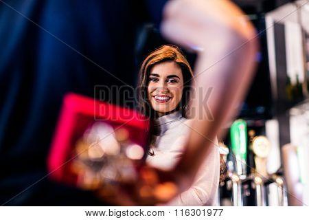 Man hiding gift box behind back in a bar