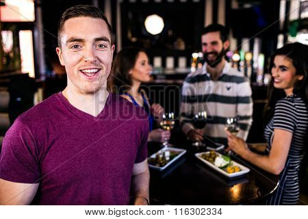 Portrait of man having a drink with friends in a bar