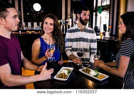 Friends having an aperitif with wine in a bar