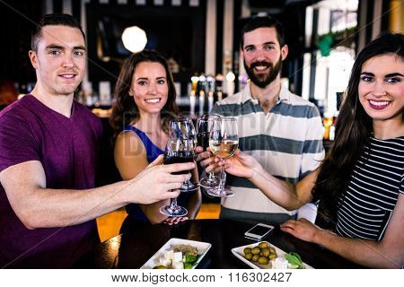 Group of friends toasting with a glass of wine in a bar