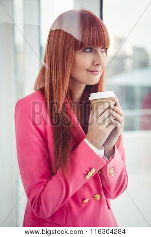 Portrait of a hipster businesswoman holding a coffee cup in office