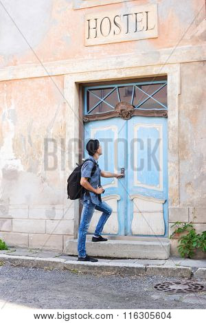 Handsome male tourist entering an old building (hostel, hotel or apartments). Traveling and couchsurfing concept.