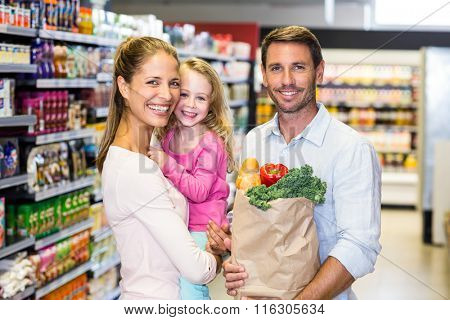 Smiling family with grocery bag at the supermarket posing for camera