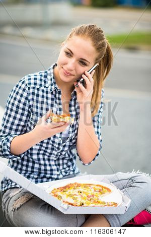Teenager eating  pizza and calling phone