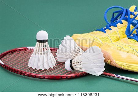 Three Badminton Shuttlecock With Racket And Shoes On Green Court