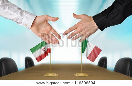 Iran and Italy diplomats shaking hands to agree deal