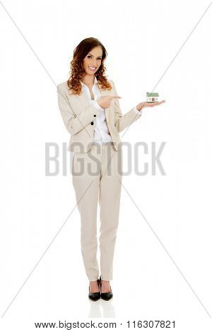 Businesswoman pointing on a model house.