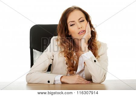 Tired businesswoman at the desk.