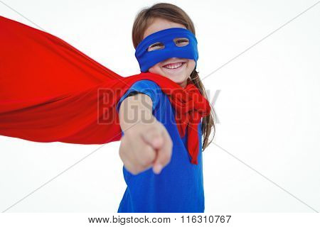 Smiling masked girl pretending to be superhero pointing at the camera on white screen