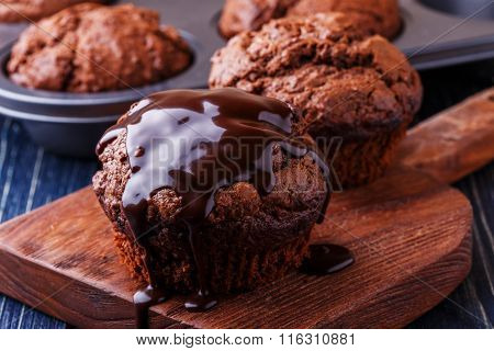 Chocolate Muffins With Chocolate Syrup On Dark Background.