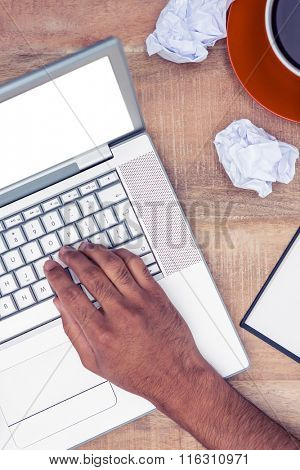 Cropped image of stressed businessman using laptop at desk in office