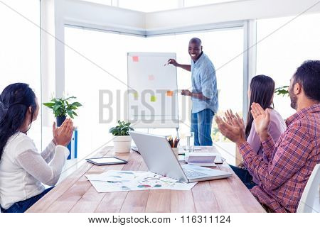 Cheerful businessman giving presentation while team applauding in creative office
