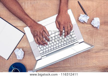 Directly shot of stressed businessman using laptop at desk in office