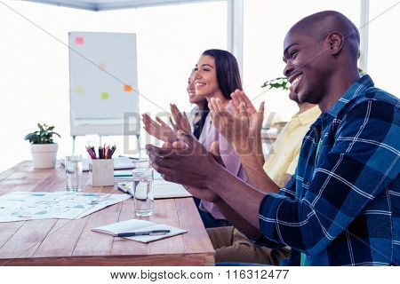 Cheerful businessman applauding in conference room at creative office