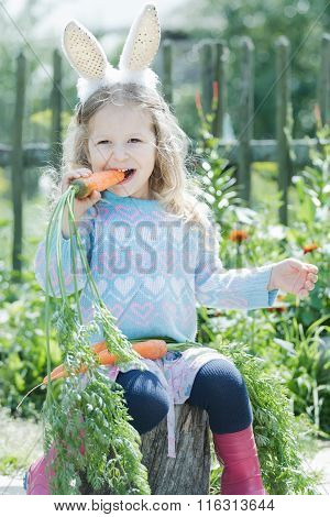 Preschooler blonde girl wearing Easter rabbit costume gnawing fresh carrot