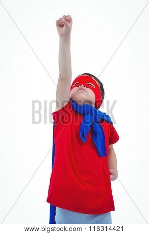 Masked boy raising fist pretending to be superhero on white screen