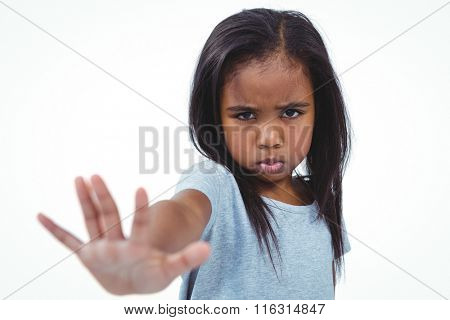 Girl making grimace holding hand to camera on white screen