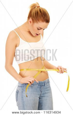 Shocked woman measuring her waist.