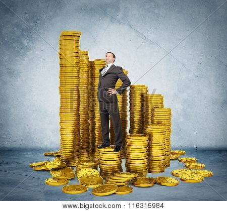 Proud businessman standing on stack of coins