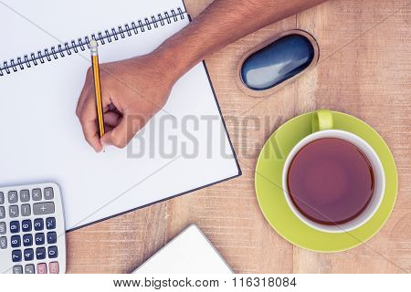 Cropped image of businessman writing on book at desk in office