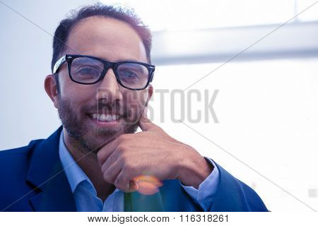 Close-up portrait of happy businessman in brightly lit creative office