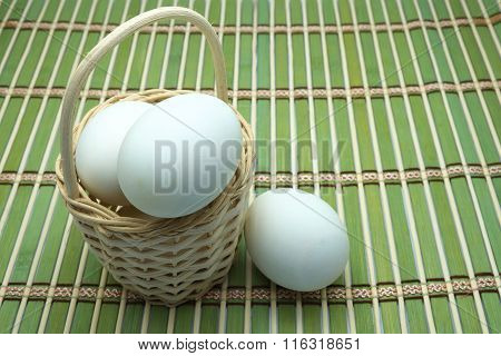 Eggs in/around wooden basket on green bamboo mat. Focus on eggs in basket.