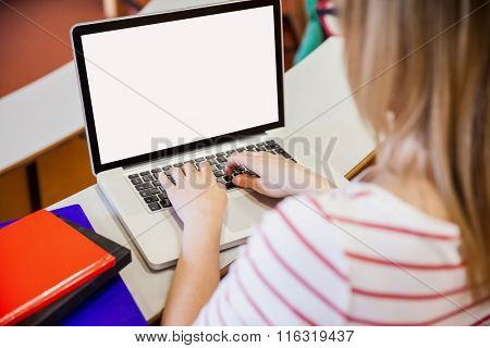 Female student typing on laptop at the university