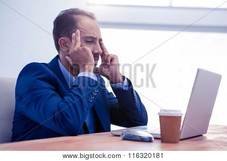 Tensed businessman working on laptop in creative office