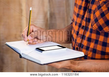 Mid section of man with smartphone writing on book against wooden wall