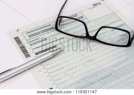 Form of income tax return with ball pen and glasses in Germany