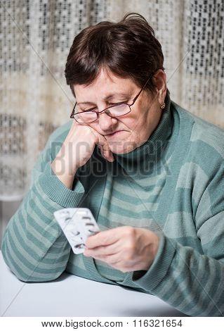Sad Senior Woman Holding  Pills