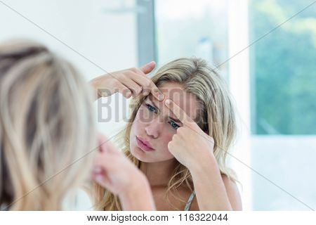 Focused beautiful young woman looking at herself in the bathroom mirror at home