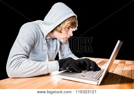 Focused man with hoodie typing on laptop with black background