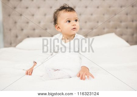 Cute baby sitting on bed looking around