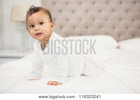 Smiling baby on bed looking around