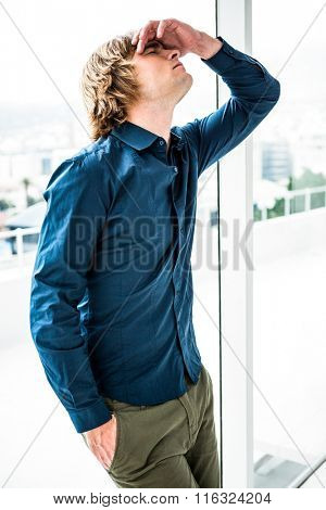 Troubled hipster businessman holding his head in his office