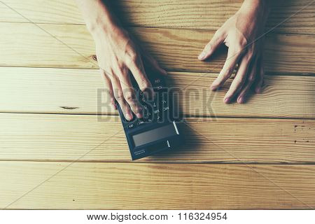 man's Hand Calculating Financial Sheet Using Calculator