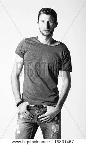 Studio Fashion Shot: Portrait Of Handsome Young Man Wearing Jeans And Shirt. Black And White