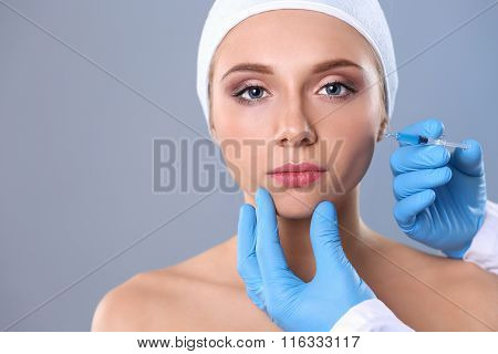 Cosmetic injection on the pretty woman face isolated on gray background