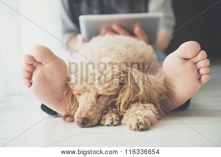 Young women is resting with a dog on the floor at home