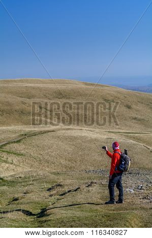 Happy Young Man Standing On Mountain.  Happy Young Tourist Man With Backpack Standing On Peak And Ta