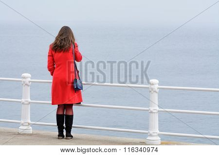 Woman With Red Coat With Black Boots Sitting In Front Of Sea. Young Woman With Red Coat Looking At W