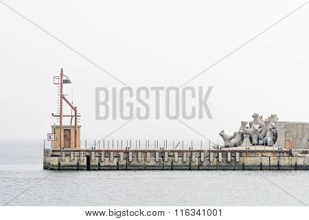 Lighthouse And Stones On Isolated Pier With Navigation Light. Calm Sea Meeting White Clear Sky And L