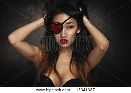 Beautiful woman with heart shape eye patch