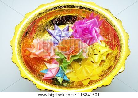 Wrapped coins with various ribbon styles in golden tray, used for ordination ceremony.